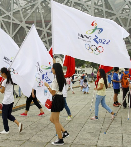 Participants holding Chinese national flags and Beijing 2022 Olympic flags walk past the Birds' Nest, also known as the National Stadium, to attend a rehearsal of a performance in Beijing