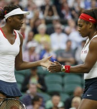 Serena Williams of the U.S. confers with her sister, Venus Williams, in the women's doubles tennis gold medal match against Czech Republic's Hlavackova and Hradecka at the London Olympic Games